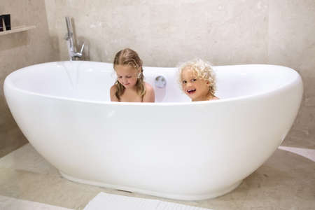 Kids taking bubble bath. Children bathing in freestanding bathtub. Little boy and girl playing with water. Hygiene for infant and baby. Child playing with soap foam in home bathroom.