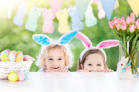 Family Easter morning. Children dye eggs. Kids with bunny ears search for candy and chocolate eggs on Easter egg hunt. Home decoration with tulip flowers, pastel rabbit banner and dye egg basket. Stock Photo