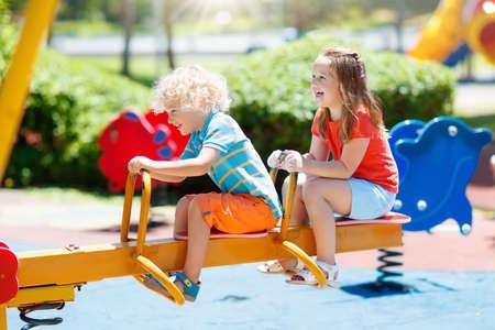 Kinder, die auf Spielplatz im Freien klettern und schieben. Kinder spielen im sonnigen Sommerpark. Aktivitäts- und Unterhaltungszentrum im Kindergarten oder Schulhof. Kind auf bunten Schaukel. Kleinkind Kind im Freien.