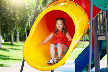 Kids climbing and sliding on outdoor playground. Children play in sunny summer park. Activity and amusement center in kindergarten or school yard. Child on colorful slide. Toddler kid outdoors. 写真素材