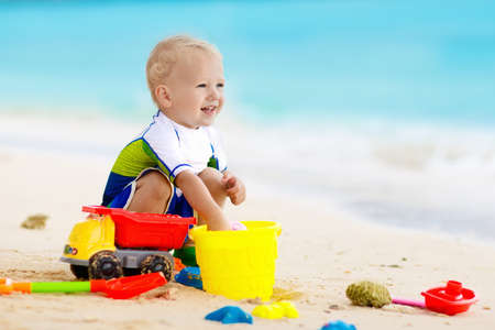 熱帯のビーチで遊ぶ子供。海岸で砂を掘っている小さな女の子。家族の夏休み。子供たちは水と砂のおもちゃで遊びます。海と島の楽しみ。幼い子