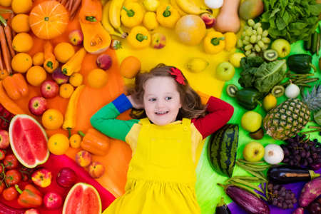 Little girl with variety of fruit and vegetable. Colorful rainbow of raw fresh fruits and vegetables. Child eating healthy snack. Vegetarian nutrition for kids. Vitamins for children. View from above. Archivio Fotografico - 96831750