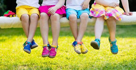 Calzado para niños. Grupo de niños en edad preescolar con coloridos zapatos de cuero. Sandalia de verano para niño y bebé. Niños en edad preescolar jugando al aire libre. Ropa infantil, calzado y moda.