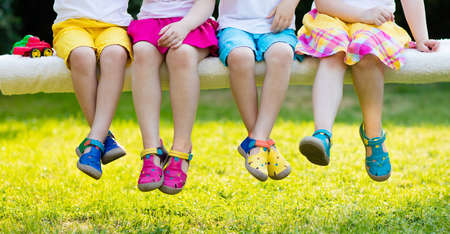Footwear for children. Group of preschool kids wearing colorful leather shoes. Sandal summer shoe for young child and baby. Preschooler playing outdoor. Child clothing, foot wear and fashion. Reklamní fotografie
