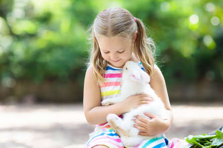 Child playing with white rabbit. Little girl feeding and petting white bunny. Easter celebration. Egg hunt with kid and pet animal. Children and animals. Kids take care of pets. Spring Easter garden. Stock Photo