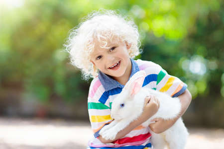 Child playing with white rabbit. Little boy feeding and petting white bunny. Easter celebration. Egg hunt with kid and pet animal. Children and animals. Kids take care of pets. Spring Easter garden. Stock Photo