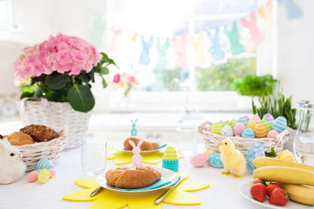 Easter breakfast table setting. Decoration for Easter family celebration. Eggs basket and spring flowers. Bread, croissant and fruit for kids meal. Egg and pastel bunny decor in kitchen at window. Zdjęcie Seryjne - 97202320