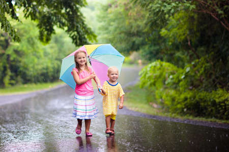 Kids playing out in the rain. Children with umbrella play outdoors in heavy rain. Little girl and boy caught in first spring shower. Kids outdoor fun by rainy autumn weather. Child in tropical storm. Stock Photo