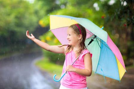 Ragazzino che gioca fuori sotto la pioggia. I bambini con l'ombrello giocano all'aperto sotto la pioggia. Bambina catturata nella prima doccia di primavera. Divertimento all'aperto per bambini in caso di tempo piovoso in autunno. Bambino che corre nella tempesta tropicale.