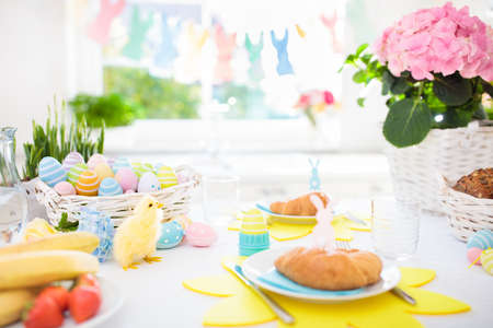 Easter breakfast table setting. Decoration for Easter family celebration. Eggs basket and spring flowers. Bread, croissant and fruit for kids meal. Egg and pastel bunny decor in kitchen at window. Banque d'images - 97202200