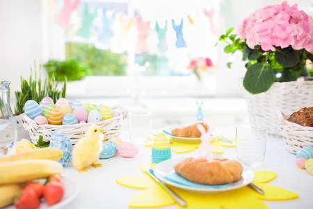 Impostazione del tavolo per la colazione di Pasqua. Decorazione per la celebrazione della famiglia pasquale. Cesto di uova e fiori primaverili. Pane, cornetto e frutta per il pasto dei bambini. Decorazione del coniglietto pastello e dell'uovo in cucina alla finestra. Archivio Fotografico - 97202200