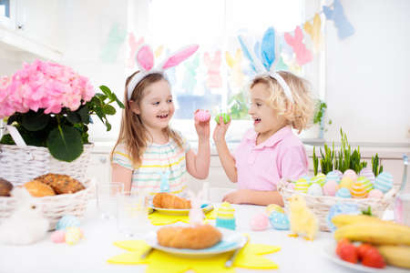 Family Easter breakfast. Child with bunny ears at decorated table with eggs basket, chick and rabbit on Easter morning. Egg hunt and meal for kids. Spring home decoration. Boy and girl with dyed eggs. Stock Photo