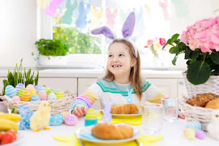 Family Easter breakfast. Child with bunny ears at decorated table with eggs basket, chick and rabbit on Easter morning. Egg hunt and festive meal for kids. Spring home decoration. Girl with dyed eggs.