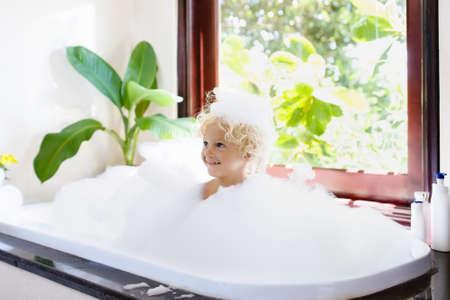 Little child taking bubble bath in beautiful bathroom with big garden view window. Kids hygiene. Shampoo, hair treatment and soap for children. Kid bathing in large tub. Baby boy with foam in hair. Standard-Bild - 97380115