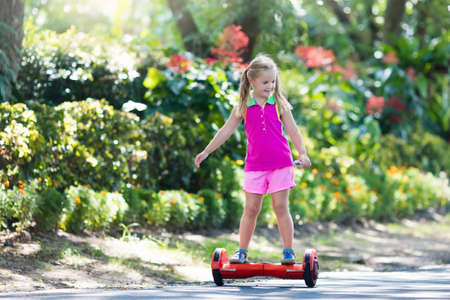Child on hover board. Kids riding scooter in summer park. Balance board for children. Electric self balancing scooter on city street. Girl learning to ride hoverboard. Modern gadgets for school kid. Stock Photo - 97380170