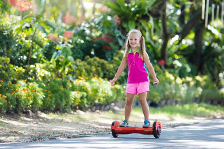 Child on hover board. Kids riding scooter in summer park. Balance board for children. Electric self balancing scooter on city street. Girl learning to ride hoverboard. Modern gadgets for school kid. Stock Photo - 97380248