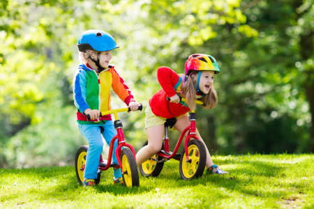Children riding balance bike. Kids on bicycle in sunny park. Little girl and boy ride glider bike on warm summer day. Preschooler learning to balance on run bicycle in safe helmet. Sport for kids. 写真素材 - 97380352