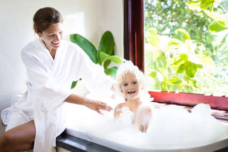 Little child taking a bubble bath in a beautiful bathroom with a big garden view window. Mother washing baby. Kids hygiene. Shampoo, hair treatment and soap foam for children. Mom bathing kid in large tub.