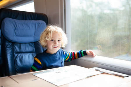 Child traveling by train. Little kid in a high speed express train on family vacation in Europe. Travel by railway. Children in railroad car. Kids in rail way wagon. Entertainment for young passenger. Reklamní fotografie