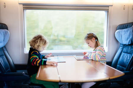Child traveling by train. Little kid in a high speed express train on family vacation in Europe. Travel by railway. Children in railroad car. Kids in rail way wagon. Entertainment for young passenger. Stock Photo