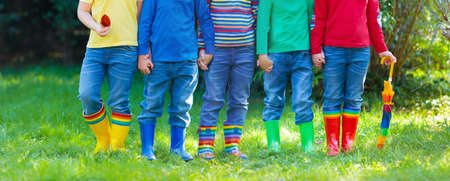 Kids in rain boots. Group of kindergarten children in colorful rubber boots and autumn jackets. Footwear for rainy fall. Foot wear for child and baby. Toddler in wellies. Rainbow gumboots. Kid fashion Foto de archivo - 99621000