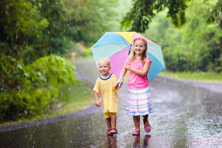 Kids playing out in the rain. Children with umbrella play outdoors in heavy rain. Little girl and boy caught in first spring shower. Kids outdoor fun by rainy autumn weather. Child in tropical storm. Foto de archivo - 99570070