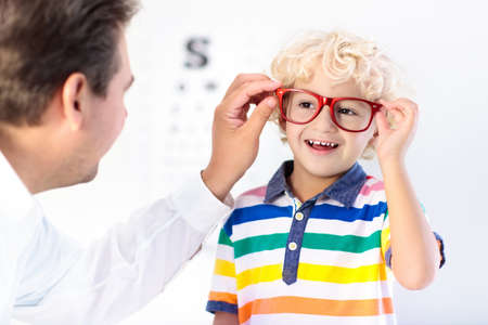 Child at eye sight test. Little kid selecting glasses at optician store. Eyesight measurement for school kids. Eye wear for children. Doctor performing eye check. Boy with spectacles at letter chart. 写真素材