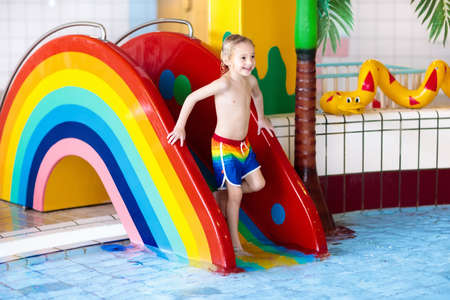Child On Swimming Pool Slide Kid Having Fun Sliding In Water Amusement Park Kids