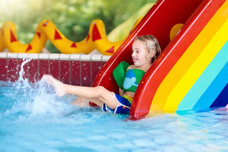 Child on swimming pool slide. Kid having fun sliding in water amusement park. Kids swim. Family summer vacation in tropical resort. Little boy in baby pool with colorful rainbow water slide. Reklamní fotografie - 99580613