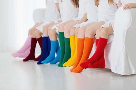 Kids wearing colorful rainbow socks. Children footwear collection. Variety of knitted knee high socks and tights. Child clothing and apparel. Kid fashion. Legs and feet of little boy and girl group. Banco de Imagens