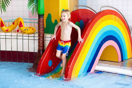 Child on swimming pool slide. Kid having fun sliding in water amusement park. Kids swim. Family summer vacation in tropical resort. Little boy in baby pool with colorful rainbow water slide.