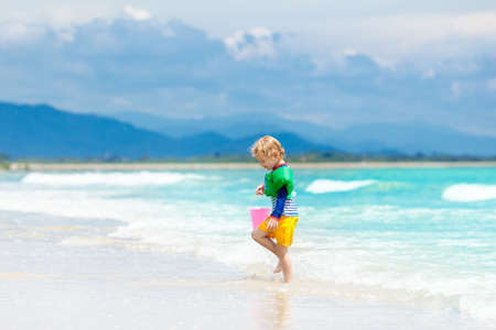 Child playing on tropical beach. Little boy digging sand at sea shore. Family summer vacation. Kids play with water and sand toys. Ocean and island fun. Travel with young children. Asia holiday. Stock Photo