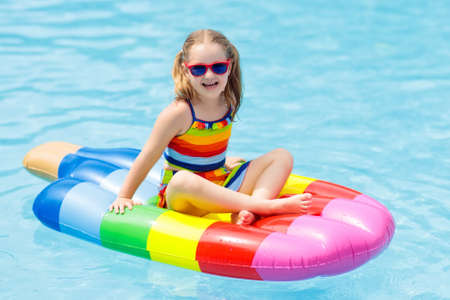 Happy child on inflatable ice cream float in outdoor swimming pool of tropical resort. Summer vacation with kids. Swim aids and wear for children. Water toys. Little girl floating on colorful raft.