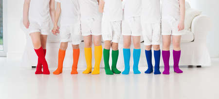 Kids wearing colorful rainbow socks. Children footwear collection. Variety of knitted knee high socks and tights. Child clothing and apparel. Kid fashion. Legs and feet of little boy and girl group. Фото со стока