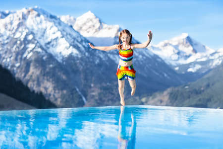 Child in outdoor infinity pool with snowy mountain in the background. Family vacation in luxury Alpine resort. Kids in the Alps mountains. Hot tub in snow. Apres ski activity for kids. Children swim.