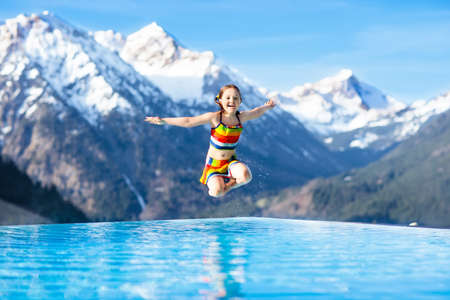 Child in outdoor infinity pool with snowy mountain in the background. Family vacation in luxury Alpine resort. Kids in the Alps mountains. Hot tub in snow. Apres ski activity for kids. Children swim. Stok Fotoğraf - 100056590