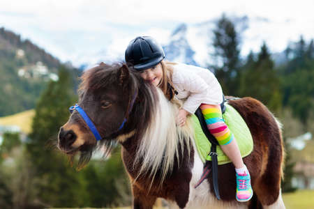Kids riding pony in the Alps mountains. Family spring vacation on horse ranch in Austria, Tirol. Children ride horses. Kid taking care of animal. Child and pet. Little girl in saddle on pony.
