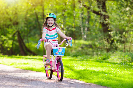 Child riding a bike in summer park. Little girl learning to ride a bicycle without training wheels. Kindergarten kid on two wheeler bike. Active outdoor sport for kids. Children cycling.