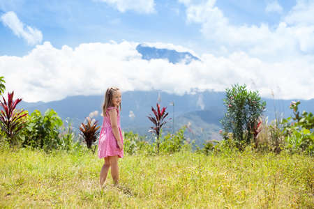 Child hiking in mountains. Kids trekking in Borneo jungle. Little girl looking at Mount Kinabalu peak, highest mountain of Malaysia. Family summer vacation in Southeast Asia.
