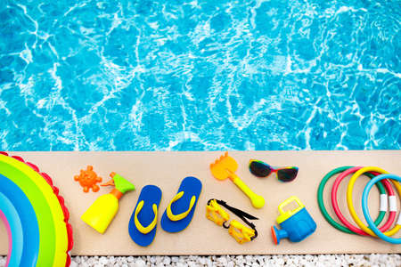 Swimming pool accessories flat lay. Top view of beach items on pool deck. Flip flops, bikini and hat, sun glasses. Water toys. Summer vacation in tropical resort. Copy space. Colorful beach wear. Фото со стока