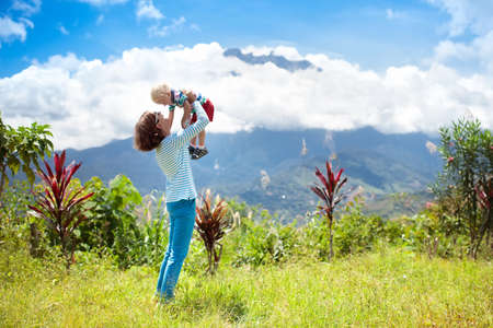 Mother and children hiking in mountains. Mom and kids trekking in Borneo jungle. Family looking at Mount Kinabalu peak, highest mountain of Malaysia. Summer vacation in Southeast Asia.