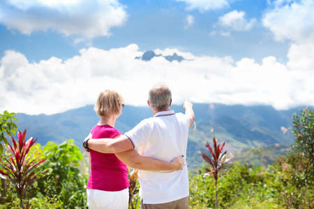Senior couple hiking in mountains. Mature man and woman trekking in Borneo jungle. Family looking at Mount Kinabalu peak, highest mountain of Malaysia. Summer vacation in Southeast Asia. Archivio Fotografico