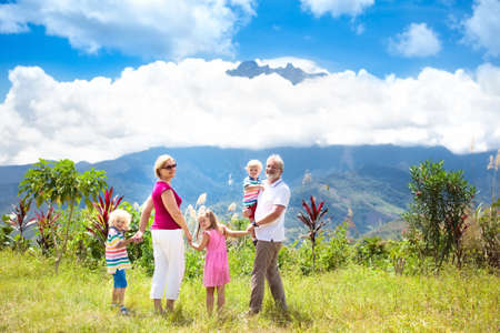 Grandparents and children hiking in mountains. Parents and kids trekking in Borneo jungle. Family looking at Mount Kinabalu peak, highest mountain of Malaysia. Summer vacation in Southeast Asia.