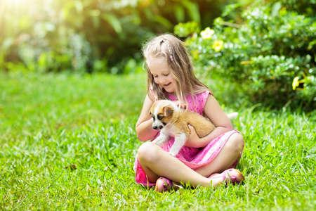 I bambini giocano con un piccolo cucciolo carino. Bambini e cuccioli di cani che giocano nel soleggiato giardino estivo. Cuccioli della holding della bambina. Bambino con cane da compagnia. Famiglia e animali domestici sul prato del parco. Amicizia di bambini e animali.