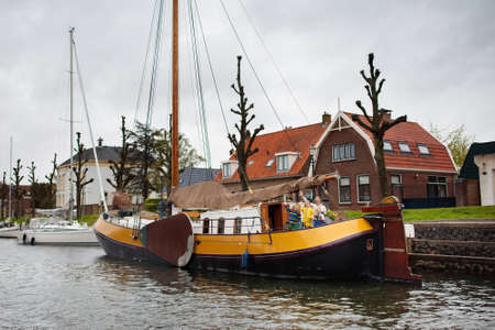 Family on boat in Holland, sailing in Amsterdam channels. Dutch family with kids on traditional residential yacht. Wooden ship in the Netherlands. Foto de archivo