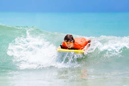Teenager boy surfing on tropical beach in Asia. Child on surf board on ocean wave. Active water sports for kids. Kid swimming with body board. Young surfer in exotic sea. Swim and eye wear for kids.