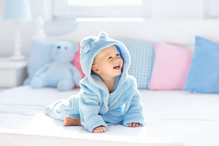 Neonato che ride felice sveglio in morbido accappatoio dopo il bagno che gioca sul letto bianco con cuscini blu e rosa nella soleggiata camera dei bambini. Bambino in asciugamano pulito e asciutto. Lavaggio, igiene infantile, salute e cura della pelle. Archivio Fotografico