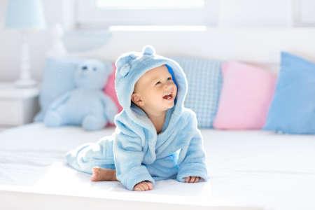 Nettes glückliches lachendes Baby im weichen Bademantel nach dem Bad, das auf weißem Bett mit blauen und rosa Kissen im sonnigen Kinderzimmer spielt. Kind in sauberem und trockenem Handtuch. Waschen, Säuglingshygiene, Gesundheit und Hautpflege. Standard-Bild