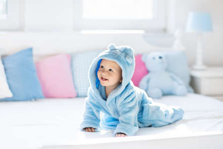 Cute happy laughing baby boy in soft bathrobe after bath playing on white bed with blue and pink pillows in sunny kids room. Child in clean and dry towel. Wash, infant hygiene, health and skin care.