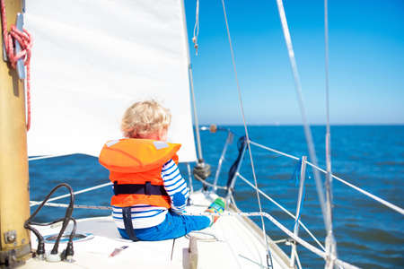 Kids sail on yacht in sea. Child sailing on boat. Little boy in safe life jackets travel on ocean ship. Children enjoy yachting cruise. Summer vacation for family. Young sailor on sailboat front deck. Stok Fotoğraf - 101183705
